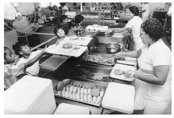 With the help of the American School Food Service Association, school cafeterias around the nation provide balanced meals, which are crucial to growing children's bodies and minds. [Photograph by Martha Tabor. Working Images Photographs.]