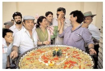 A Spanish celebration featuring paella, a rice and seafood dish served here in a giant paellera. Saffron, a spice from the Muslim countries to the south and east, gives the dish its yellow color. [Photograph by Owen Franken. Corbis. Reproduced by permission.]