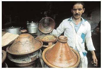 North African cuisine reflects the Islamic traditions of the region. Here, a man cooks with traditional Moroccan tajines, conical clay pots used for lamb stews and curries. [Photograph by Owen Franken. Corbis. Reproduced by permission.]